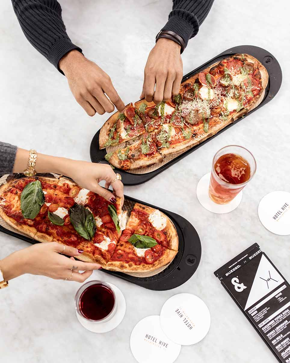 four hands grabbing two elongated slizes of pizza on a table top with two glasses
