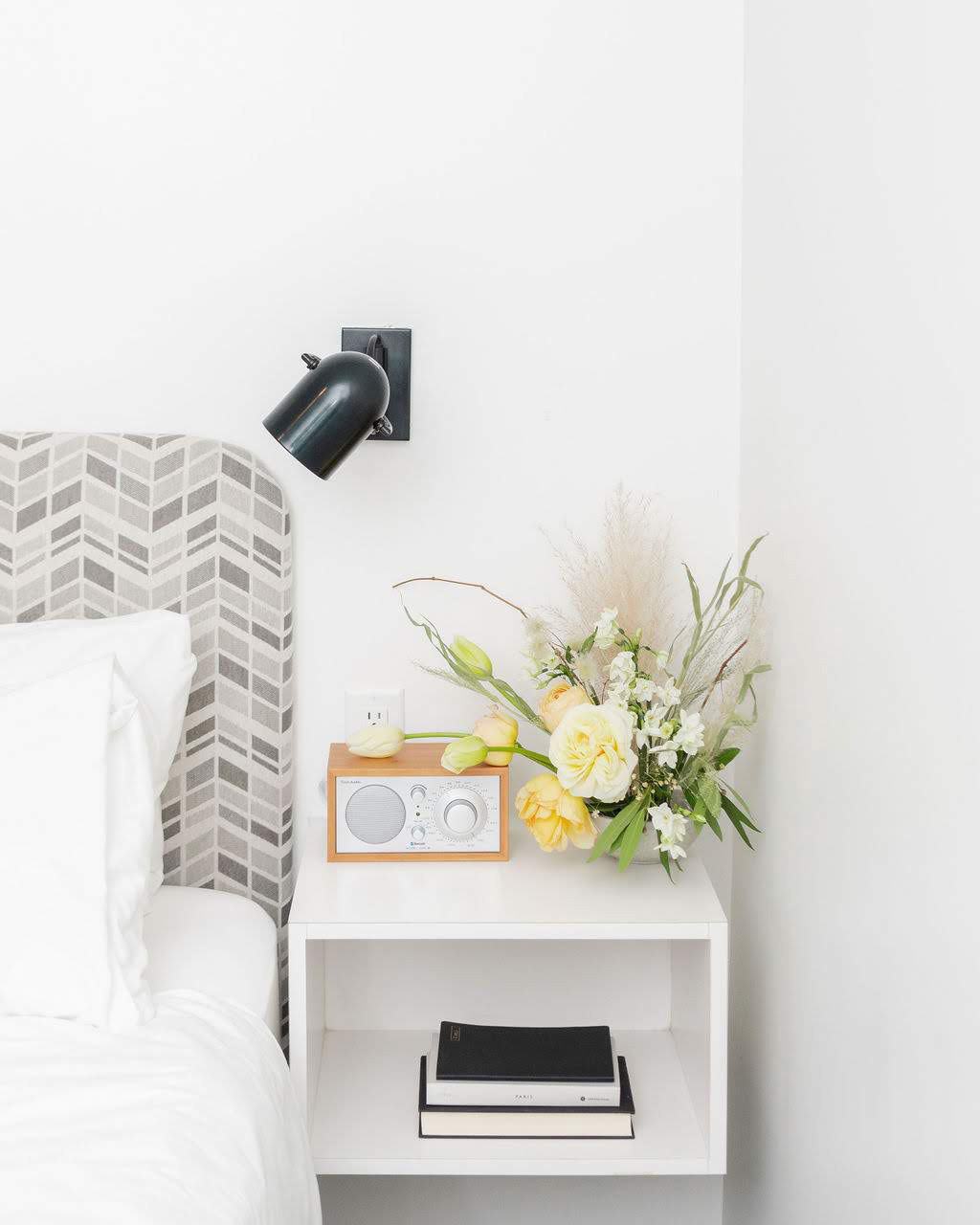 night stand with flower arrangement and partial view of bed/headboard