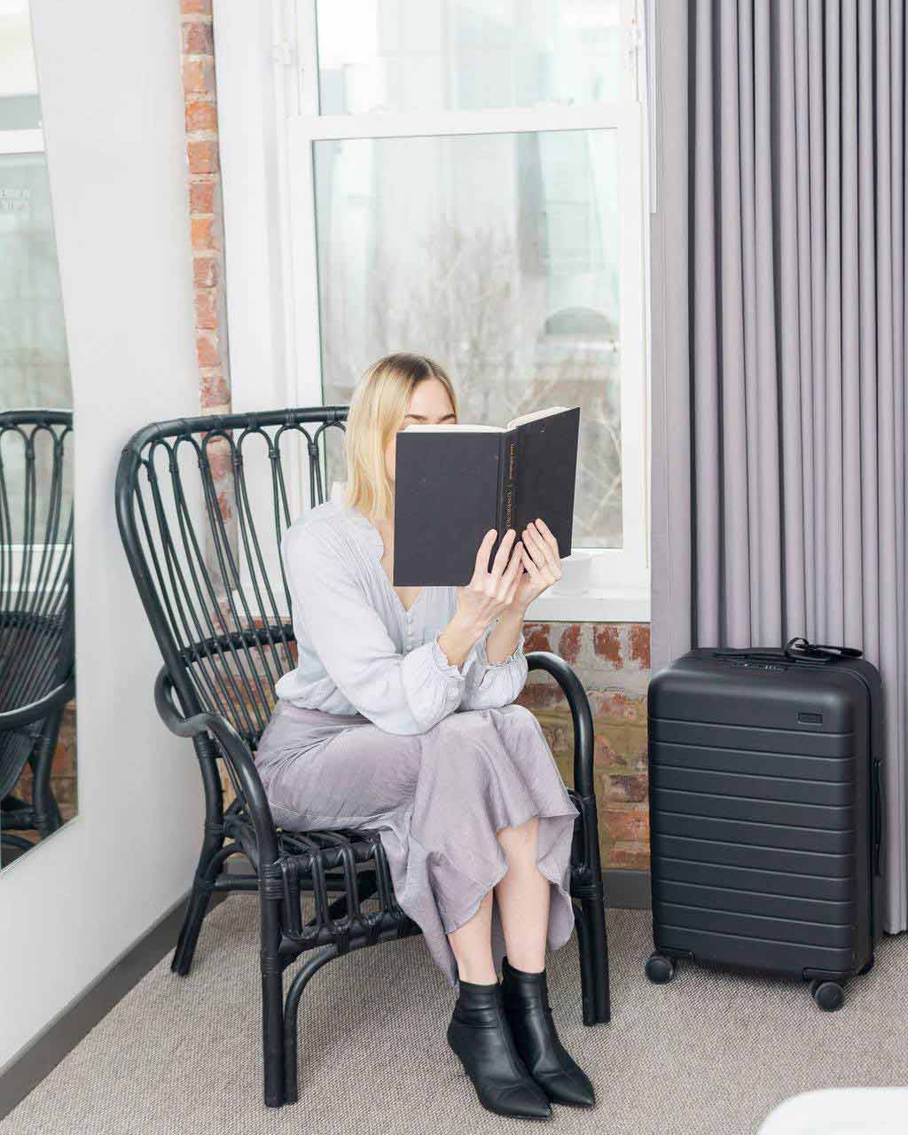 stylish woman reading sitting straight on a chair, next to suitcase