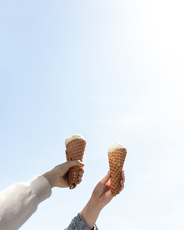 two hands holding up two ice cream cones